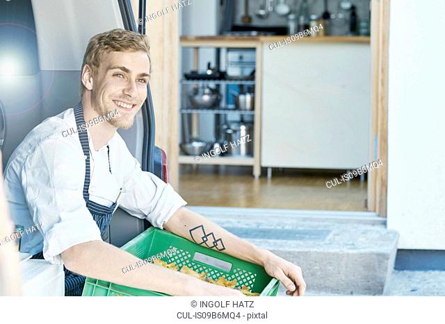 Chef in commercial kitchen looking away smiling