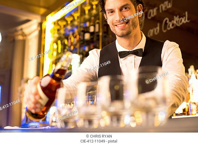 Portrait of well dressed bartender pouring bourbon in luxury bar