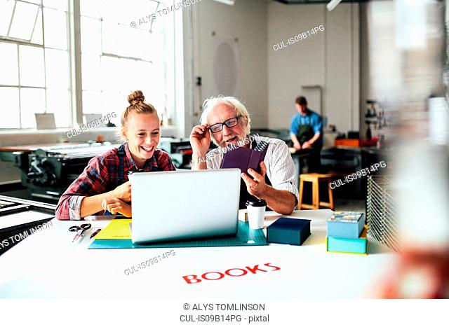 Senior male craftsman laughing and looking at laptop with young woman in book arts workshop