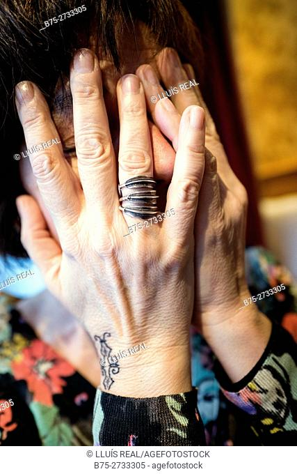Woman covering her face with her hands, hand with a ring and tattoo