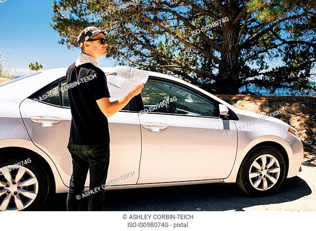 Man on road trip reading map, Big Sur, California, USA