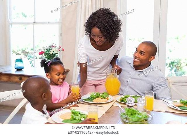 Mother serving juice to her family at lunch