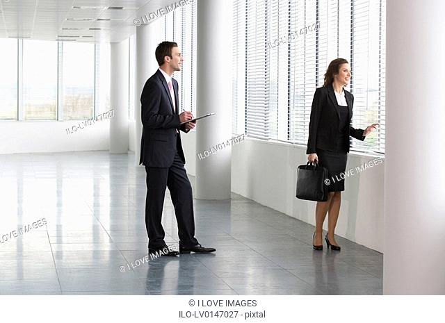 A letting agent showing businesswoman around empty office