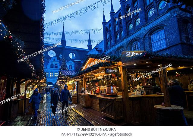 During the continous rainfall, only few visitors walk the grounds of the Christmas market in Luebeck, Germany, 27 November 2017