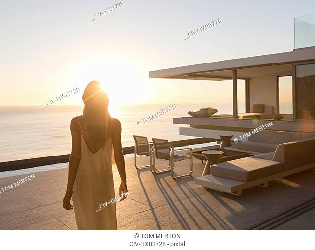 Woman walking on tranquil sunset modern, luxury home showcase exterior patio with ocean view