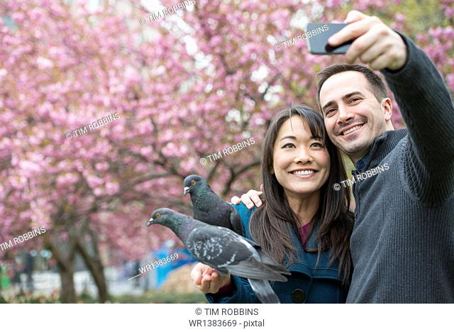 A couple, a man and woman, in the park, taking a selfy, self portrait with a mobile phone. Two pigeons perched on her wrist