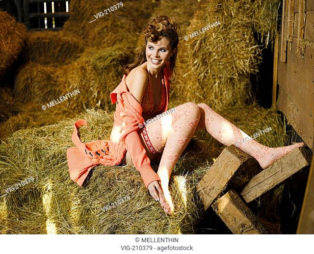 Young woman sitting on hay bales in a stable.  - G³ltlingen, GERMANY, 30/08/2005