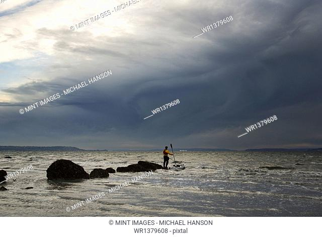 A man stands on a rock in the middle of the Puget Sound with his sea kayak floating next to him