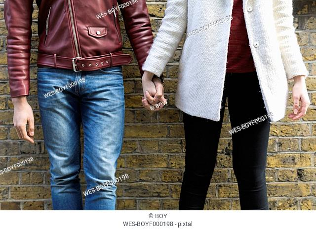Close-up of couple hand in hand in front of brick wall