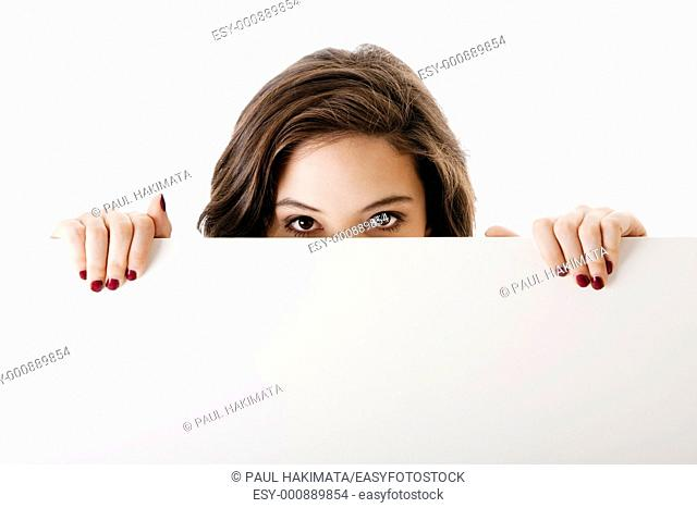 Partial face of beautiful young caucasian brunette business student woman holding a white blank board, isolated