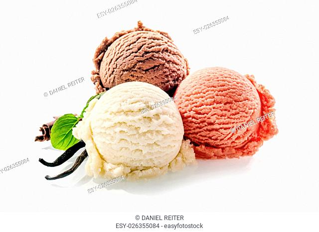 Trio of colorful frozen dessert on a white background decorated with two vanilla pods chocolate shavings and mint