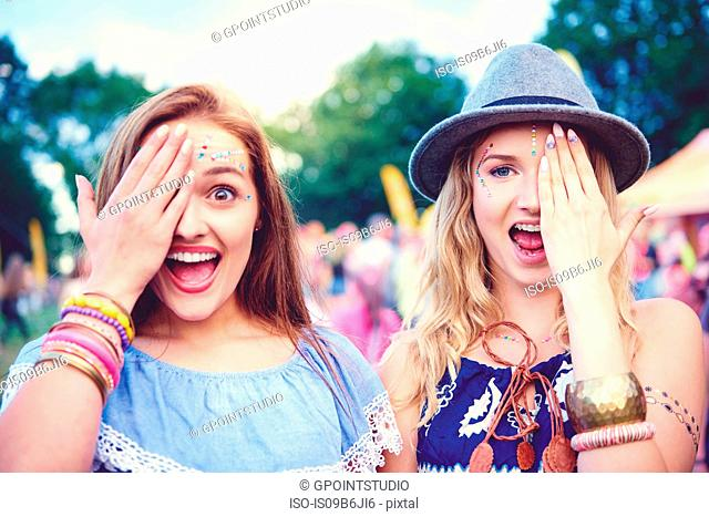 Portrait of two young female friends covering an eye at festival