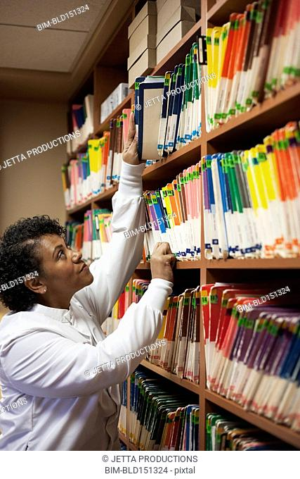 Mixed race dentist selecting medical files in office