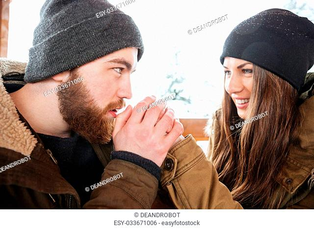 Handsome careful bearded young man warming his girlfriend hands in winter