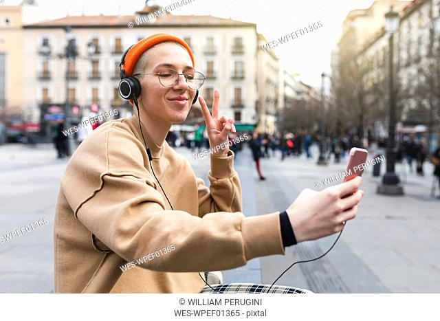 Young woman taking a selfie while listening to music and making peace gesture with her hand