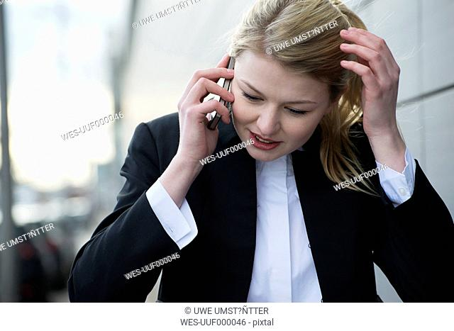 Germany, Mannheim, Young businesswoman using mobile phone