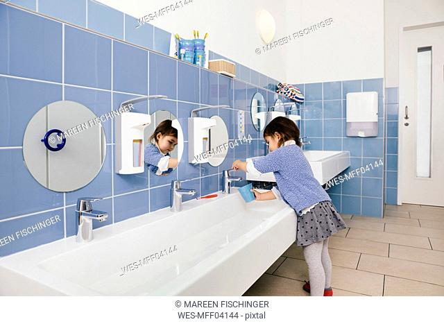 Little girl using water for brushing her teeth in bathroom of a kindergarten