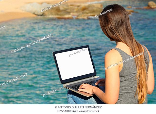 Woman using laptop showing blank screen on a beautiful beach on summer vacation