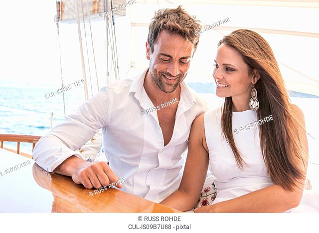 Couple relaxing on yacht, on water