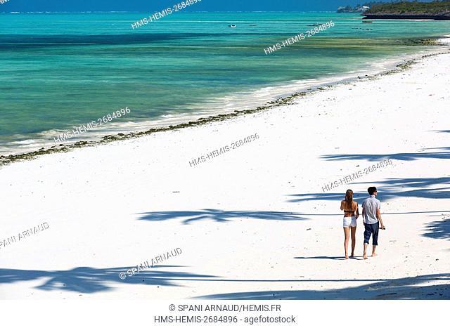 Tanzania, Zanzibar, Jambiani, tourist couple walking on the sandy beach