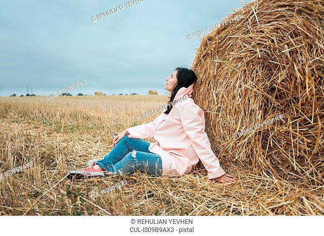 Woman in raincoat by hay bale, Odessa, Ukraine