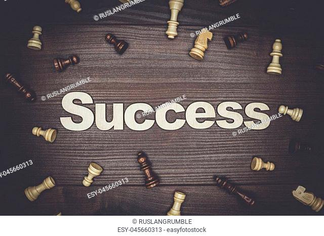 word success and chessmen on the brown wooden background