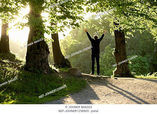 Man standing with arms up in forest