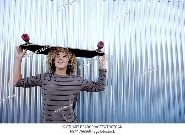 Teenage boy holding a longboard on his head