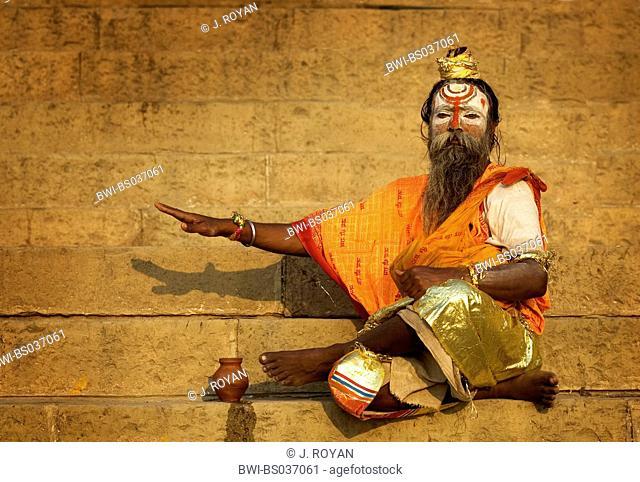 holy man, sadhu, on a stair at a Ghat, a sacred bath place, India, Varanasi