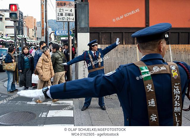 23. 12. 2017, Kyoto, Japan, Asia - Traffic wardens are seen regulating the flow of traffic at an intersection in Kyoto's old city