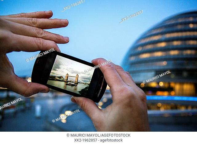 Detail of hands Taking a picture of Tower Bridge with a mobile phone, London, UK