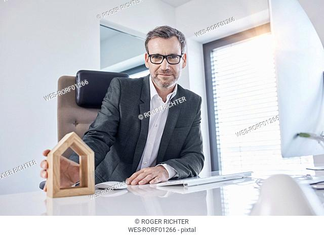 Portrait of businessman at desk in office with architectural model
