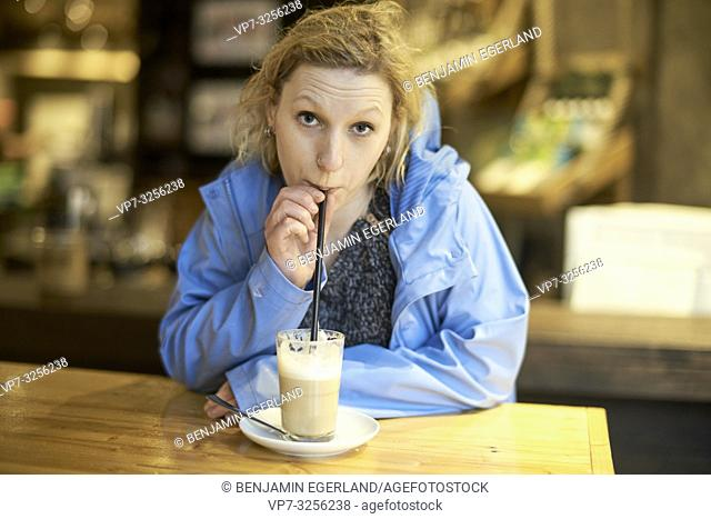 Young woman drinking latte macchiato in café, drawing drinking straw, in Munich, Germany