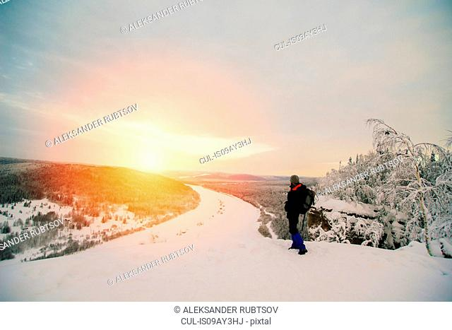 Man on snow covered landscape looking at view of sunset over frozen river