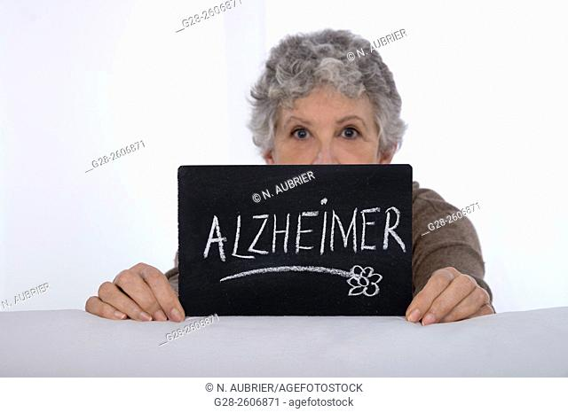 Senior Woman with grey hair holding a black slate with Alzheimer written on it