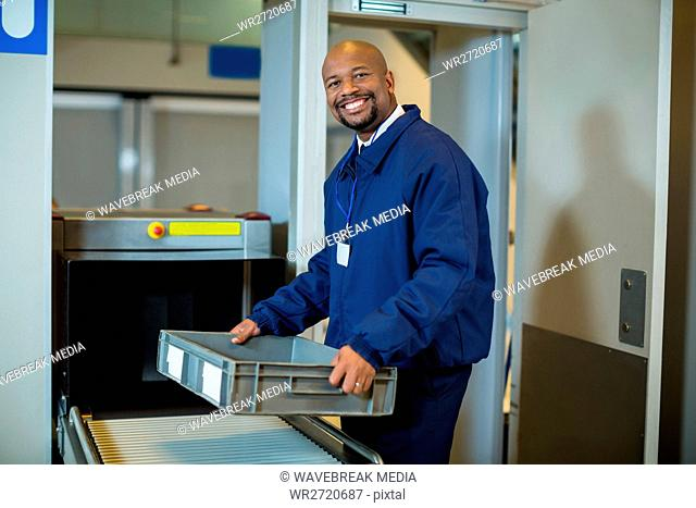 Smiling airport security officer holding a crate near conveyor belt