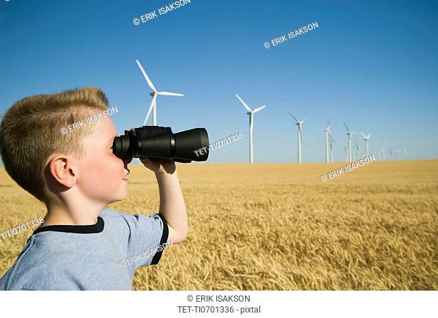 Boy on wind farm looking through binoculars
