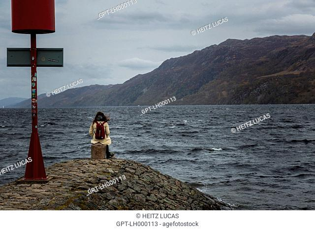 VISITORS SITTING ON A DYKE IN THE WIND BY THE BANKS OF LOCH NESS, MOUNTAINS IN THE BACKGROUND, LOCH NESS, INVERNESS, HIGHLANDS, SCOTLAND, UNITED KINGDOM
