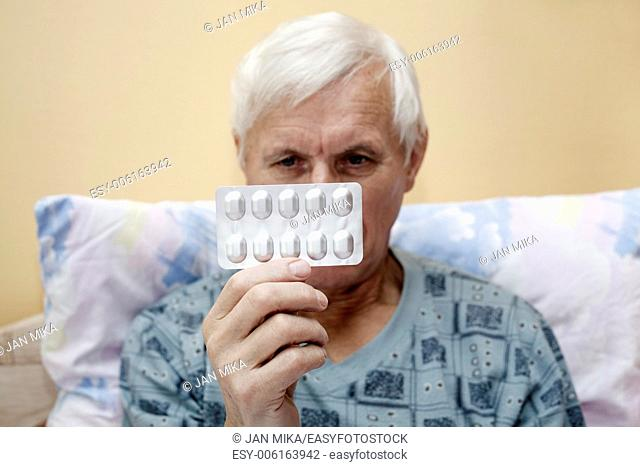 Ill senior man looking at pills