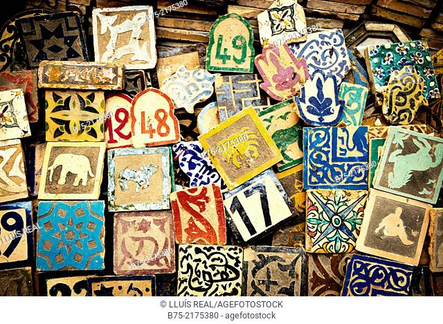 Close-up of a ceramic tile with the numbers 17, 12, 48, 49, 9 and drawings in a typical Moroccan pottery shop in Fez Medina, Morocco, Africa