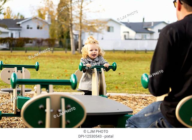 A cute young girl playing on a seesaw with her dad in a playground during the fall season; Spruce Grove, Alberta, Canada