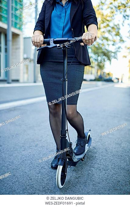 Close-up of businesswoman with scooter on the road