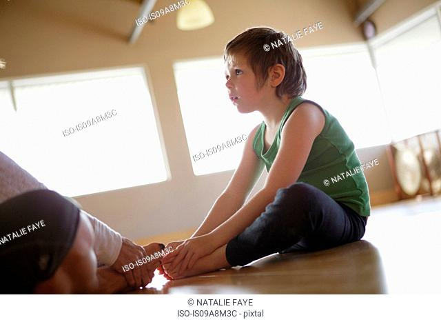 Young girl with mother practicing yoga indoors
