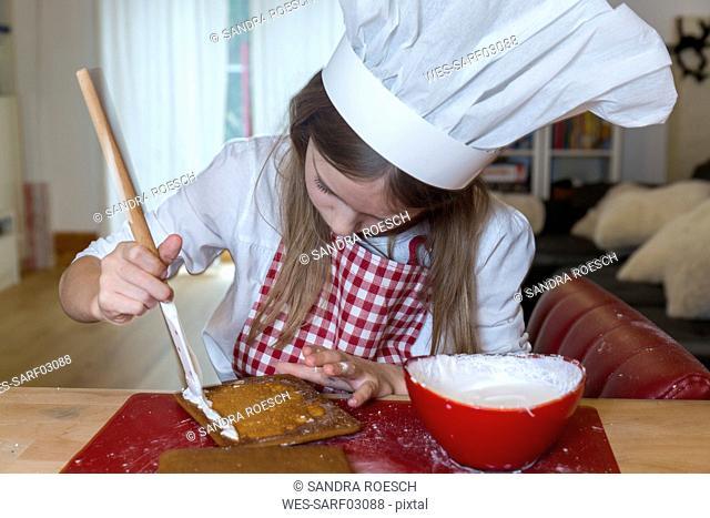 Girl preparing gingerbread house