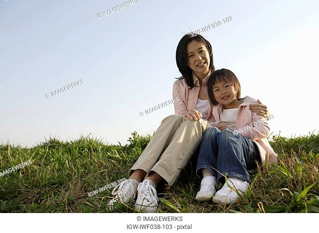 Portrait of a mother sitting with daughter on grass