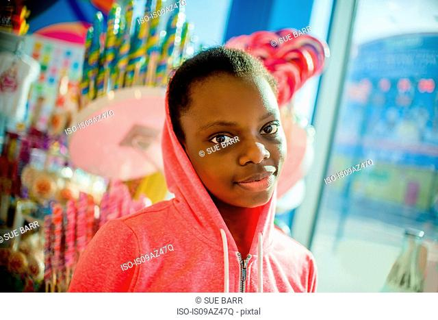 Portrait of teenage girl wearing pink hoody in candy shop, Brooklyn, USA