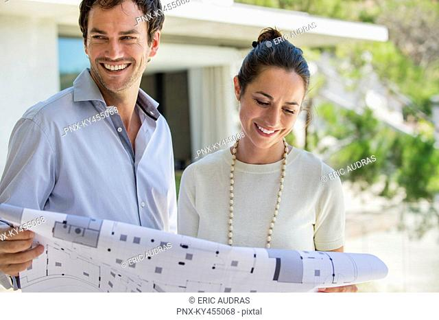 Couple holding a blueprint and smiling