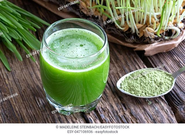 A glass of barley grass juice, with fresh and powdered plant in the background