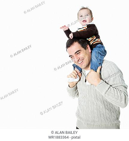 Father carrying son (2-3) on shoulders, studio shot