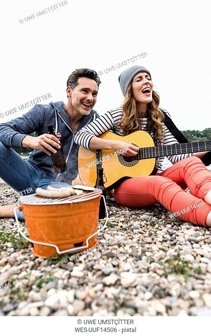 Happy couple with beer bottle, guitar and grill relaxing on pebble beach